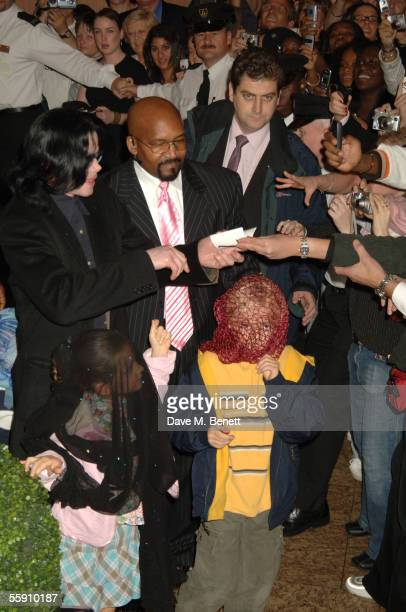 Singer Michael Jackson greets fans as he walks with his children Prince and Paris while visiting Harrods October 12 2005 in London England