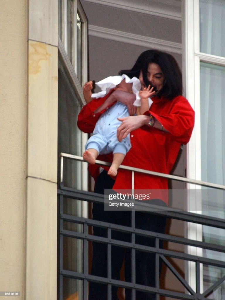 Singer Michael Jackson holds his son eightmonthold son Prince Michael II over the balcony of the Adlon Hotel November 19 2002 in Berlin Germany...