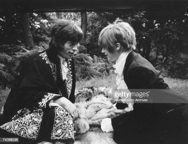 Singer Mick Jagger and his girlfriend singer Marianne Faithfull pose for a portrait in a park in 1968 in London England