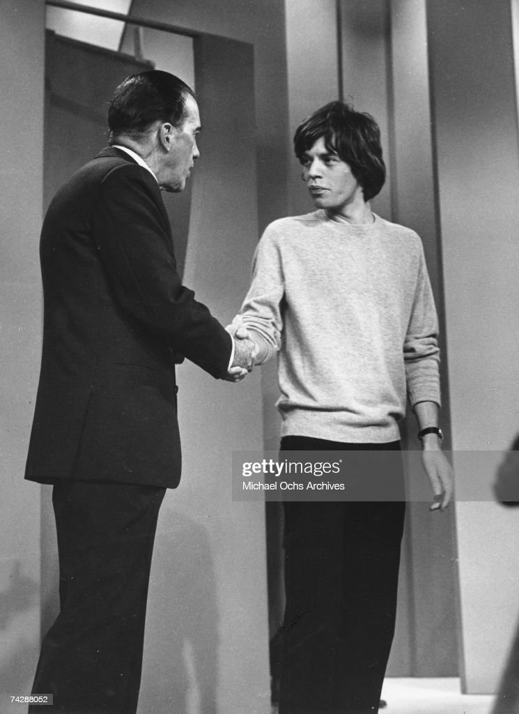 Singer Mick Jagger of the rock and roll band 'The Rolling Stones' is greeted by Ed Sullivan after performing on the Ed Sullivan Show on October 25, 1964 in New York City, New York.