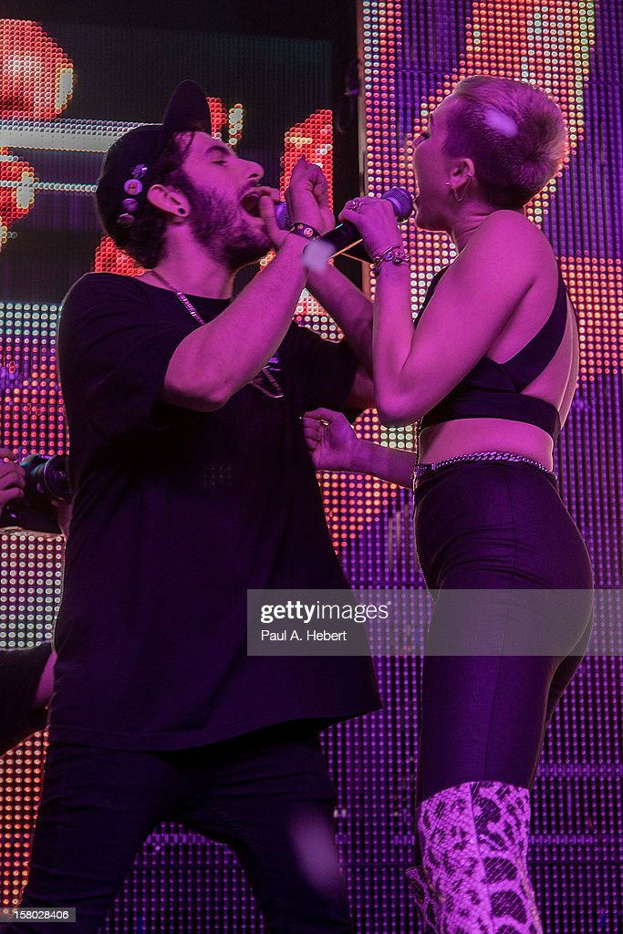 Singer Miley Cyrus and DJ Borgore perform on stage during Borgore's 'Christmas Creampies' concert at the Fonda Theatre on December 8, 2012 in Hollywood, California.
