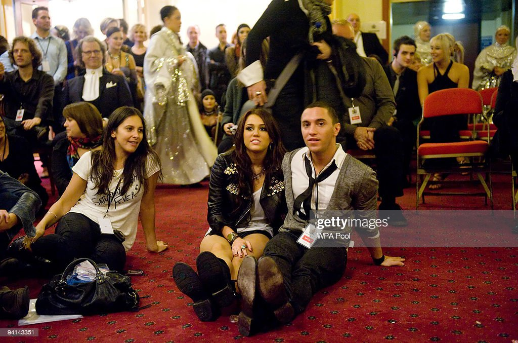 US singer Miley Cyrus (C) watches the show from backstage at the Royal Variety Performance on December 7, 2009 in Blackpool, England