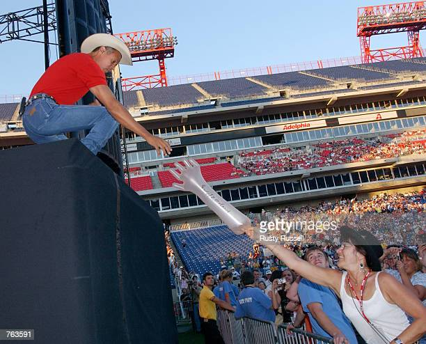 Singer Neal McCoy reaches for a gift from a fan during his performance at FanFair the world's largest country music festival June 15 2002 in...