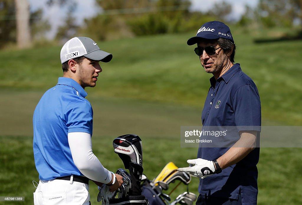 Singer Nick Jonas (L) talks with actor Ray Romano during Aria Resort & Casino's 13th Annual Michael Jordan Celebrity Invitational at Shadow Creek on April 5, 2014 in North Las Vegas, Nevada.