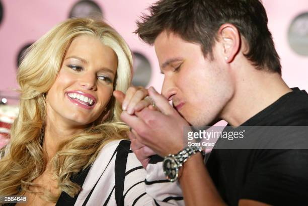 Singer Nick Lachey kisses the hand of wife Jessica Simpson at a press conference to launch Dessert an edible fragrance and body care line at...