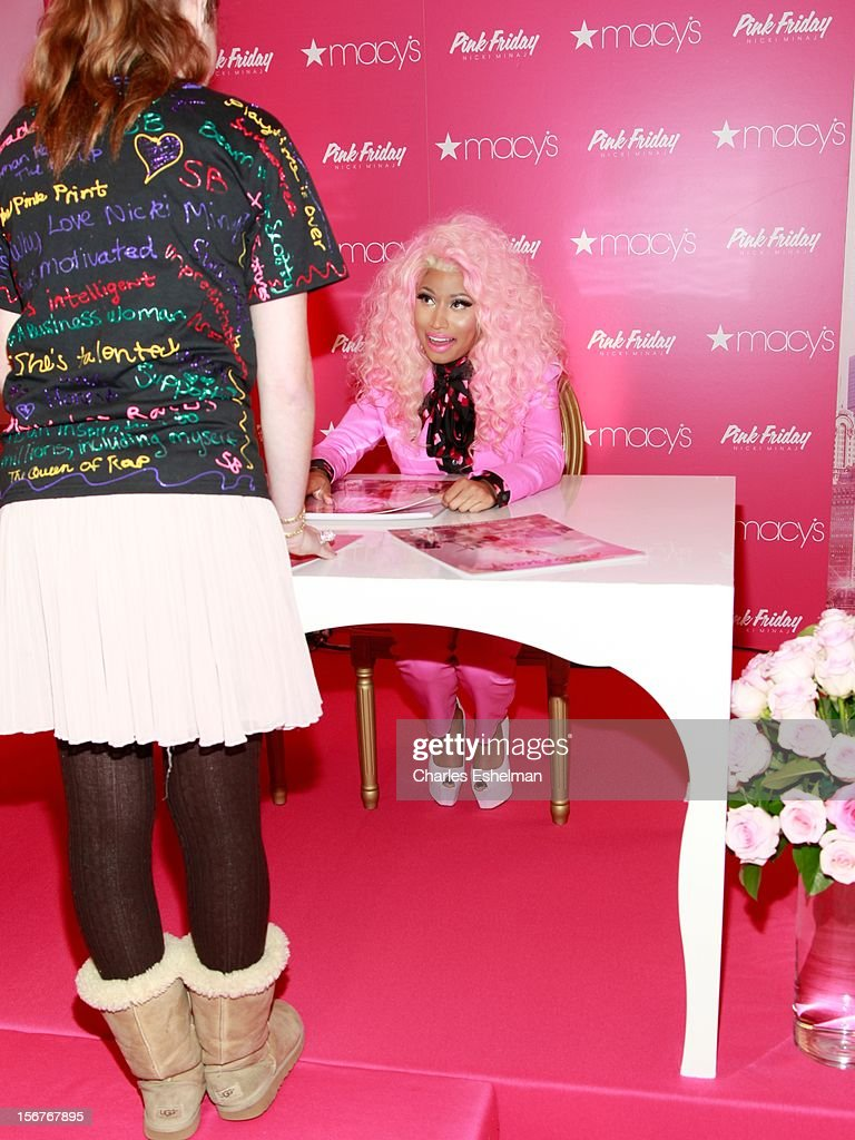 Singer <a gi-track='captionPersonalityLinkClicked' href=/galleries/search?phrase=Nicki+Minaj+-+K%C3%BCnstlerin&family=editorial&specificpeople=6362705 ng-click='$event.stopPropagation()'>Nicki Minaj</a> autographs posters at 'Pink Friday' Fragrance Holiday Season Celebration at Macy's Queens Center on November 20, 2012 in the Queens borough of New York City.