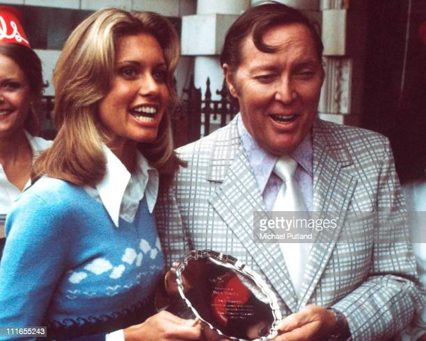 Singer Olivia Newton John presenting an award from MCA Records to American rock and roll singer and guitarist Bill Haley London 1974 The award is for...