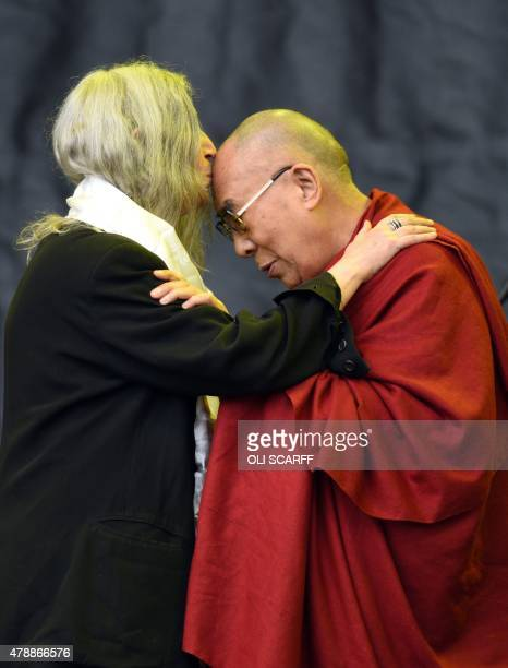 US singer Patti Smith kisses the Dalai Lama during her performance on the Pyramid Stage as he visits the Glastonbury Festival of Music and Performing...