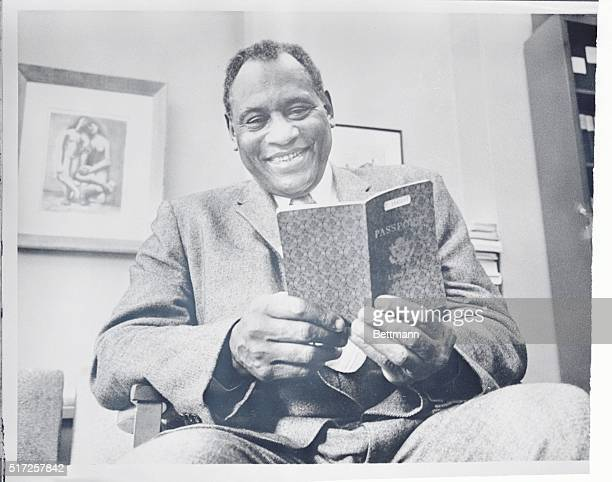 Singer Paul Robeson smilingly examines his new passport at the office of his lawyer Leonard B Boudin here This ended Robeson's eight year struggle to...