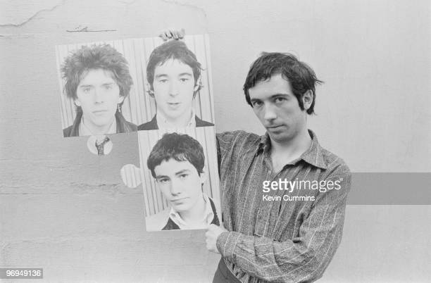 Singer Pete Shelley of English punk band the Buzzcocks holds up photographs of fellow band members Steve Garvey Steve Diggle and John Mayer in...