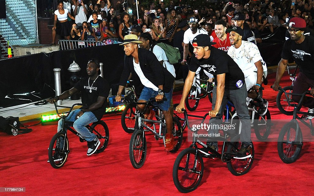 Singer <a gi-track='captionPersonalityLinkClicked' href=/galleries/search?phrase=Pharrell+Williams&family=editorial&specificpeople=161396 ng-click='$event.stopPropagation()'>Pharrell Williams</a> (2nd L) is seen at the 'VMA' on is bike on August 25, 2013 in New York City.