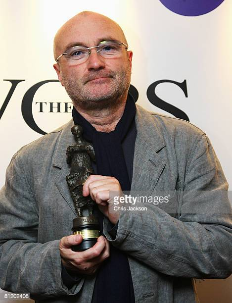 Singer Phil Collins holds his award for 'Best International Achievement' backstage at the 53rd Ivor Novello Awards At the Dorchester Hotel on May 22...