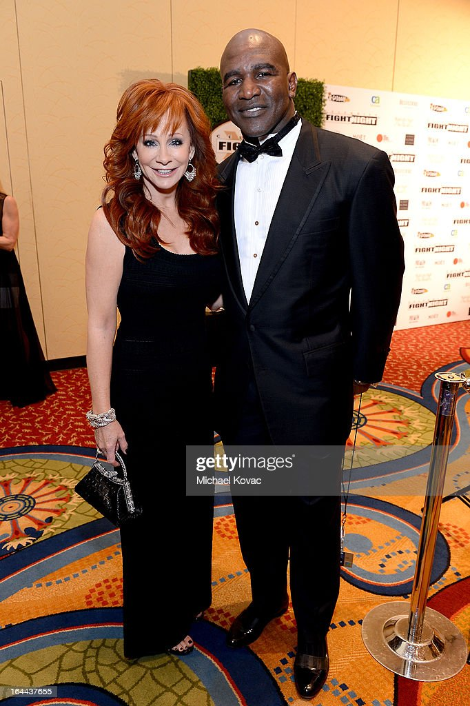 Singer <a gi-track='captionPersonalityLinkClicked' href=/galleries/search?phrase=Reba+McEntire&family=editorial&specificpeople=202959 ng-click='$event.stopPropagation()'>Reba McEntire</a> and Boxer <a gi-track='captionPersonalityLinkClicked' href=/galleries/search?phrase=Evander+Holyfield&family=editorial&specificpeople=194938 ng-click='$event.stopPropagation()'>Evander Holyfield</a> with Moet & Chandon at Celebrity Fight Night XIX at JW Marriott Desert Ridge Resort & Spa on March 23, 2013 in Phoenix, Arizona.