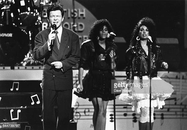 Singer Rick Astley performing on stage with his two backing singers circa 1987