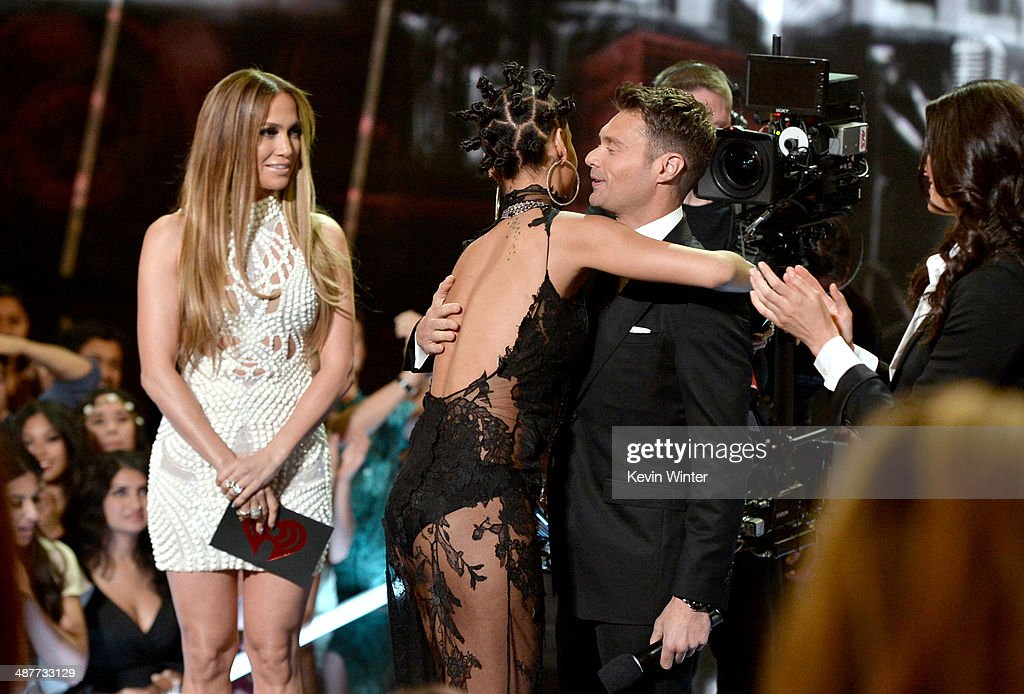 Singer Rihanna (C) accepts the Artist of the Year award from singer Jennifer Lopez (L) and TV personality Ryan Seacrest (R) onstage during the 2014 iHeartRadio Music Awards held at The Shrine Auditorium on May 1, 2014 in Los Angeles, California. iHeartRadio Music Awards are being broadcast live on NBC.