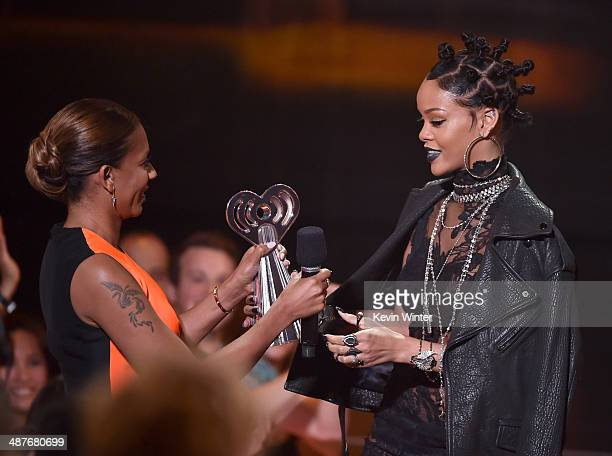 Singer Rihanna accepts the Best Fan Army award onstage from singer Mel B during the 2014 iHeartRadio Music Awards held at The Shrine Auditorium on...