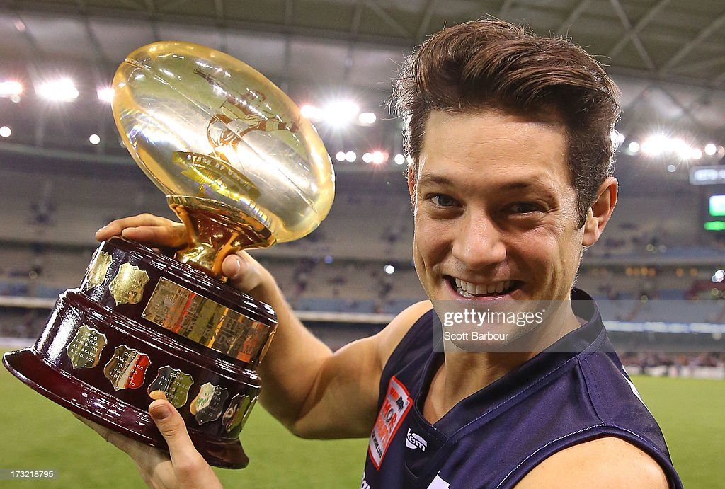 Singer <a gi-track='captionPersonalityLinkClicked' href=/galleries/search?phrase=Rob+Mills+-+Musician&family=editorial&specificpeople=242952 ng-click='$event.stopPropagation()'>Rob Mills</a> of Victoria poses with the trophy after the EJ Whitten Legends AFL game between Victoria and the All Stars at Etihad Stadium on July 10, 2013 in Melbourne, Australia.