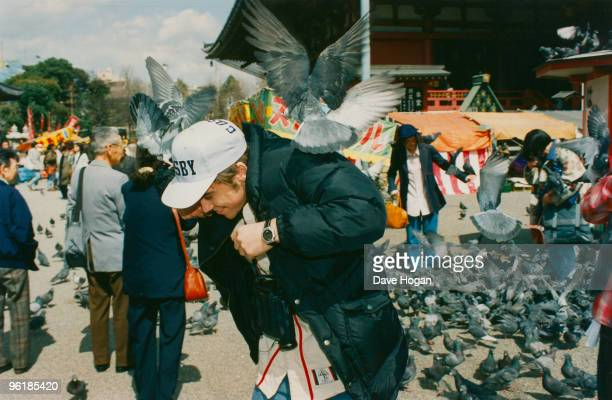 Singer Robbie Williams of English boy band Take That is beset by pigeons during a visit to Japan circa 1995