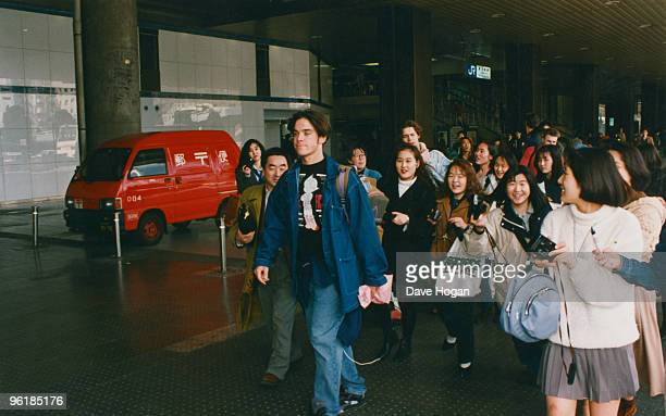Singer Robbie Williams of English boy band Take That is followed by teenage fans during a visit to Japan circa 1995