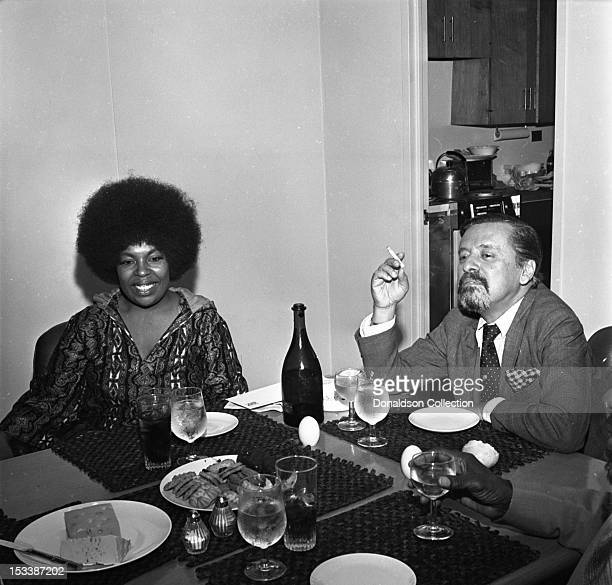 Singer Roberta Flack and Atlantic Records executive Nesuhi Ertegun look over a magazine article during a luncheon to celebrate her signing to...