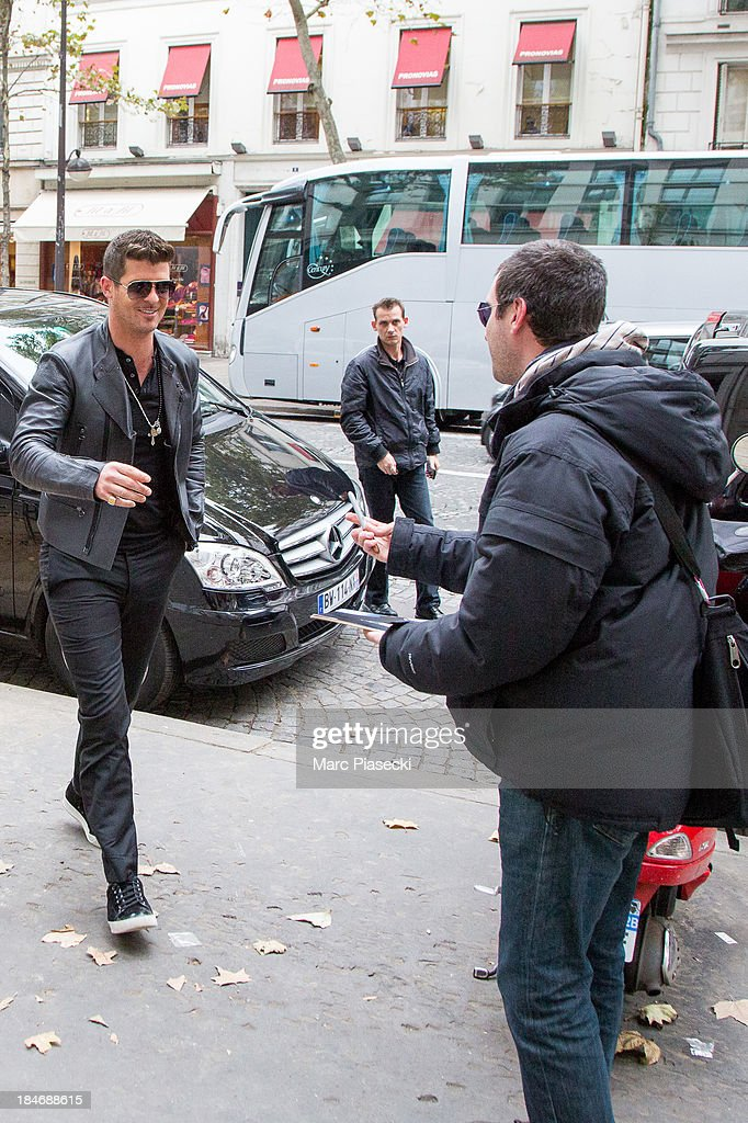 Singer <a gi-track='captionPersonalityLinkClicked' href=/galleries/search?phrase=Robin+Thicke&family=editorial&specificpeople=724390 ng-click='$event.stopPropagation()'>Robin Thicke</a> is seen signing an autograph for a fan on October 15, 2013 in Paris, France.