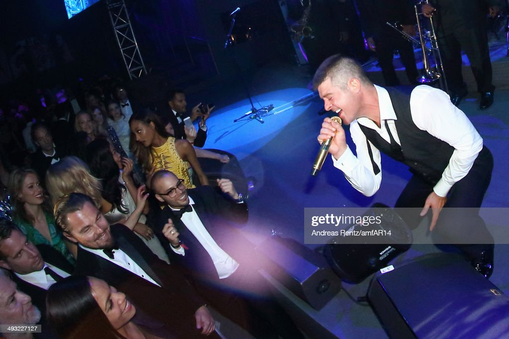 Singer <a gi-track='captionPersonalityLinkClicked' href=/galleries/search?phrase=Robin+Thicke&family=editorial&specificpeople=724390 ng-click='$event.stopPropagation()'>Robin Thicke</a> performs on stage as <a gi-track='captionPersonalityLinkClicked' href=/galleries/search?phrase=Leonardo+DiCaprio&family=editorial&specificpeople=201635 ng-click='$event.stopPropagation()'>Leonardo DiCaprio</a> and <a gi-track='captionPersonalityLinkClicked' href=/galleries/search?phrase=Rosario+Dawson&family=editorial&specificpeople=201472 ng-click='$event.stopPropagation()'>Rosario Dawson</a> smile during amfAR's 21st Cinema Against AIDS Gala Presented By WORLDVIEW, BOLD FILMS, And BVLGARI at Hotel du Cap-Eden-Roc on May 22, 2014 in Cap d'Antibes, France.