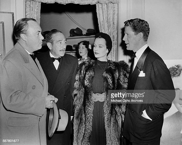 Singer Rudy Vallee with actress Hedy Lamarr talk with actor Adolphe Menjou during an event in Los Angeles California