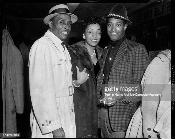 Singer Sam Cooke standing with woman and man inside B M Restaurant Pittsburgh Pennsylvania c 1963