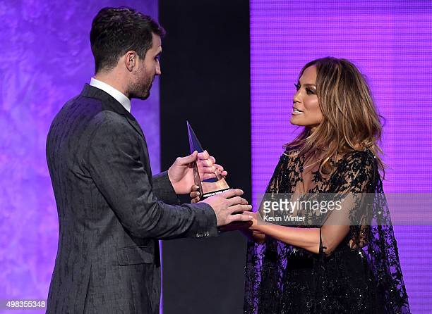 Singer Sam Hunt accepts New Artist of the Year award from host Jennifer Lopez onstage during the 2015 American Music Awards at Microsoft Theater on...