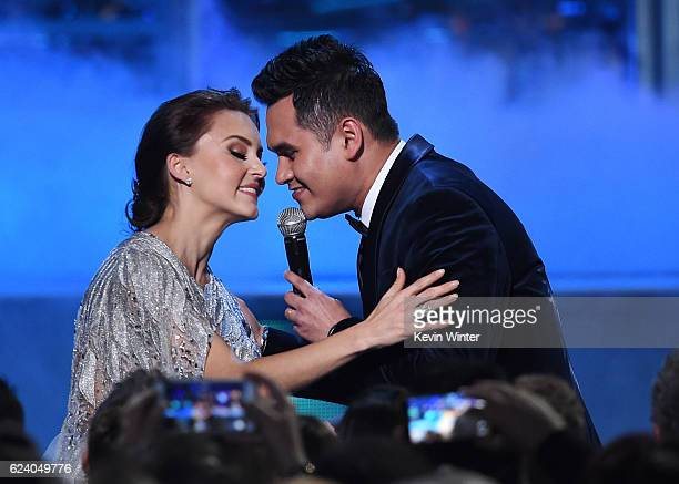 Singer Samuel Sarmiento of Banda los Recoditos performs with actress Angelique Boyer in the audience during The 17th Annual Latin Grammy Awards at...