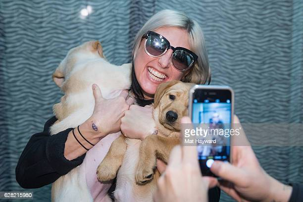 Singer Sarah Barthel of Phantogram holds two puppies brought by animal rescue organization Motley Zoo during Deck The Hall Ball hosted by 1077 the...