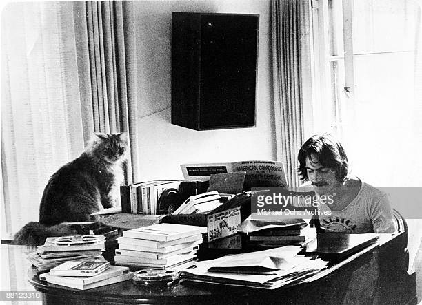 Singer songwriter James Taylor poses for a portrait at a piano piled high with books and a cat named 'Pudding' for his manager record producer...