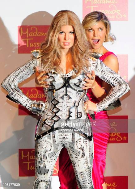 Singer Stacy 'Fergie' Ferguson of the Black Eyed Peas poses with her wax figure after it was unveiled at Madame Tussauds Las Vegas at The Venetian on...