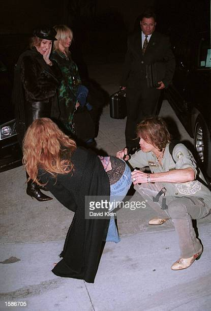 Singer Steven Tyler of Aerosmith autographs a fan's jeans outside the Sunset Marquis hotel on November 4 2002 in Hollywood California