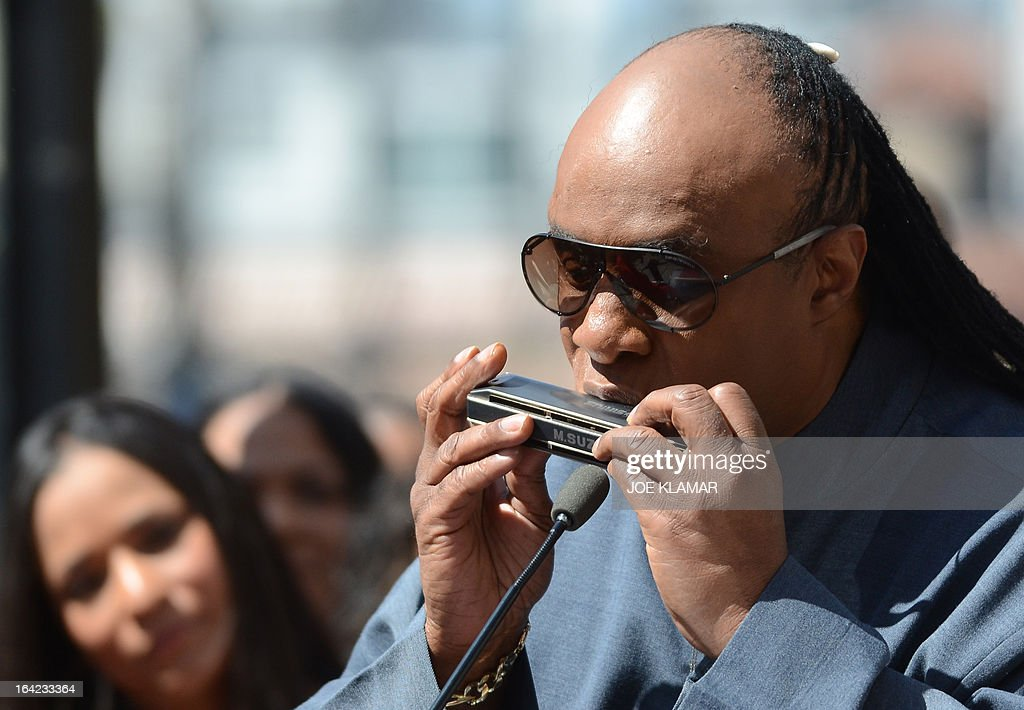 Singer Stevie wonder plays a harmonica as Jack Ashford and Eddie Willis (not pictured), surviving members of the Funk Brothers, attend a ceremony honoring the musicians with a star on the Hollywood Walk of Fame on March 21, 2013 in Hollywood, California.The Funk Brothers was the nickname of Detroit, Michigan, session musicians who performed the backing to most Motown recordings from 1959 until the company moved to Los Angeles in 1972.