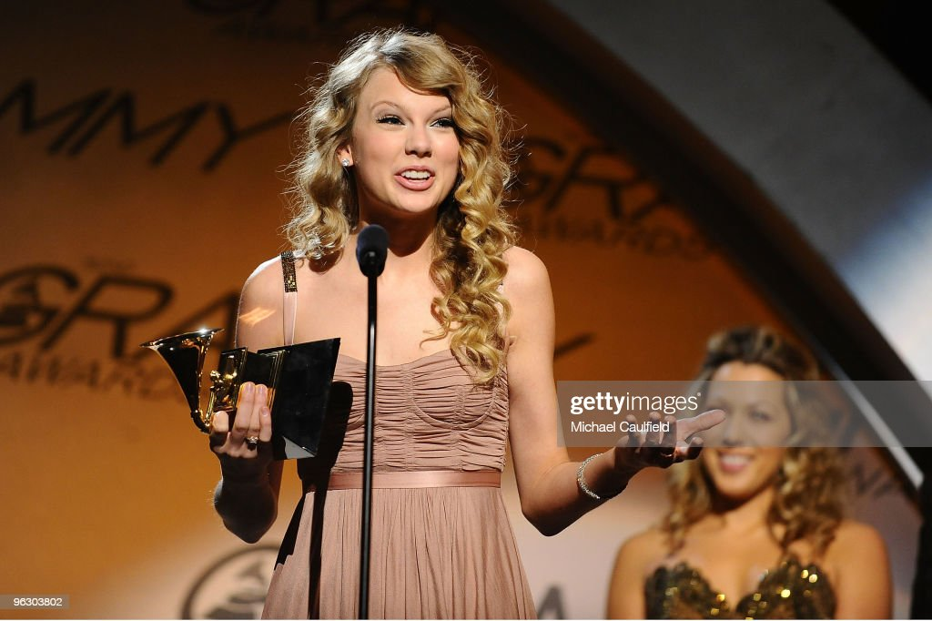 Singer Taylor Swift accepts an award as singer Colbie Caillat stands in the back during the 52nd Annual GRAMMY Awards pretelecast held at Staples...