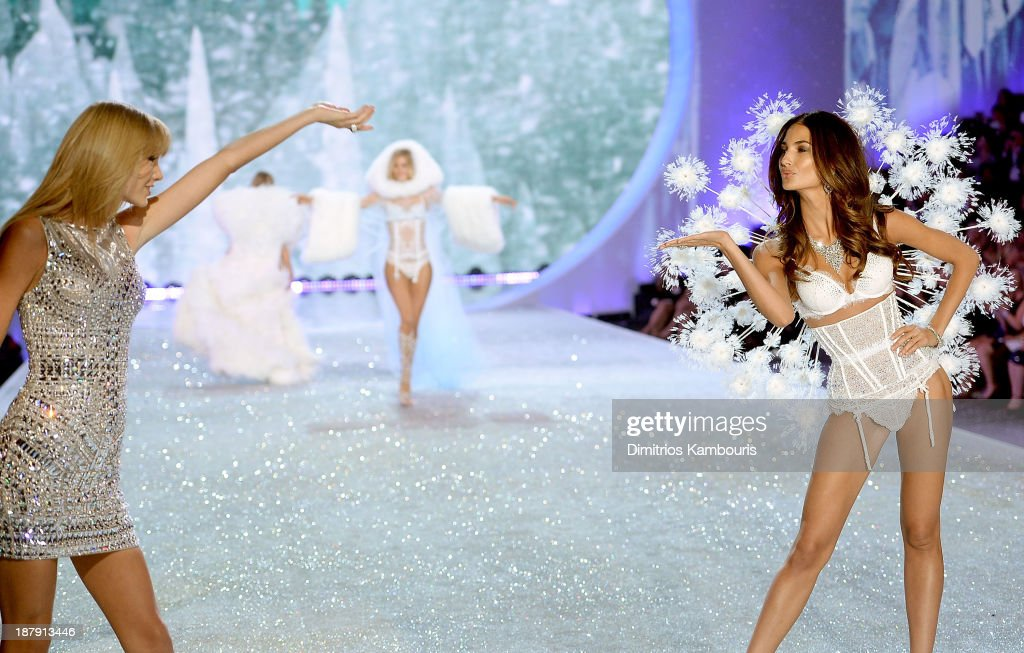 Singer Taylor Swift (L) performs and model Lily Aldridge walks the runway at the 2013 Victoria's Secret Fashion Show at Lexington Avenue Armory on November 13, 2013 in New York City.