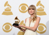 Singer Taylor Swift poses with her trophy for best song written for visual media for 'Safe and Sound' in the press room at the Staples Center during...