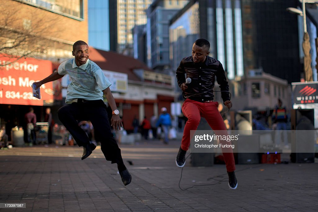 Singer Thembinkosi (R) entertains shoppers as daily life continues as former president Nelson Mandela remains in critical condition on July 13, 2013 in Johannesburg, South Africa. Former South African President Nelson Mandela has been hospitalized at the Medi-Clinic Hospital in Pretoria for five weeks. His wife Graca Machel has said she was less anxious about his condition on July 12, five weeks after he was admitted to hospital.