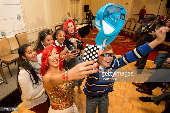 Singer Tina Tores poses for a selfie with attendees of the Foundation for Autism Acceptance Worldwide's annual fundraiser on December 11 2016 in...