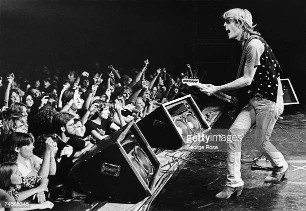 Singer Tom Petty backed by his band The Heartbreakers prances onstage during a 1980 Santa Cruz California concert at the Civic Auditorium