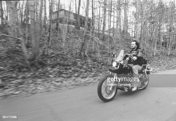 C/W singer Travis Tritt riding his HarleyDavidson motorcycle on road nr home