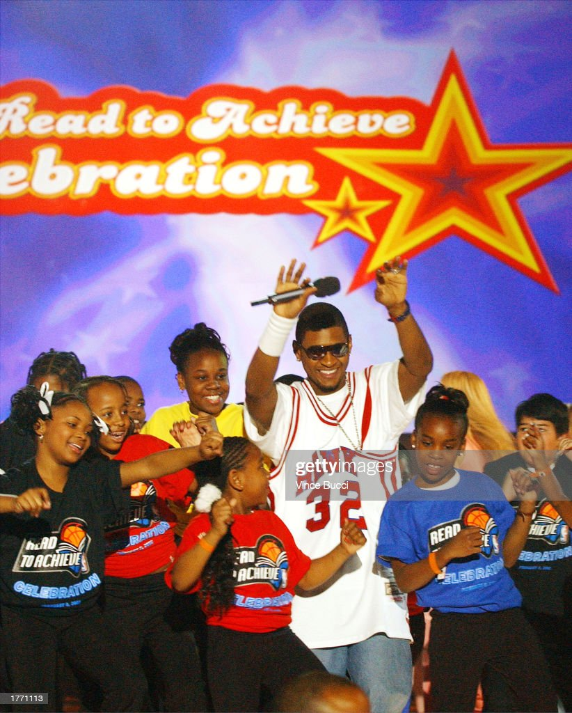 Singer Usher and kids sing and dance onstage during the NBA AllStar Jam Session event 'Read to Achieve' celebration on February 8 2003 at the Georgia...