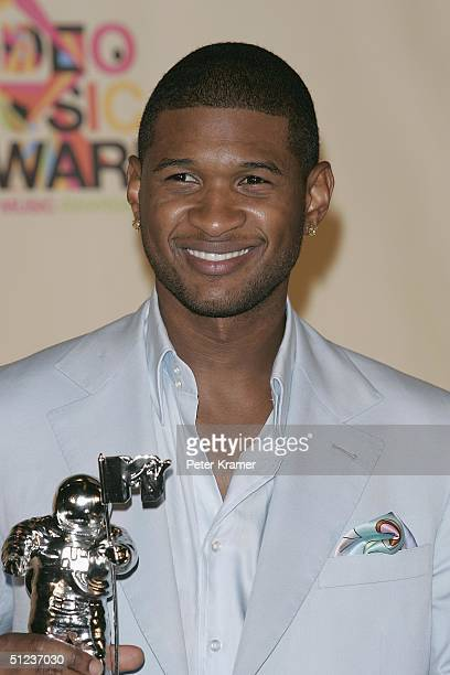 Singer Usher poses with his awards for Best Male and Best Dance in the press room at the 2004 MTV Video Music Awards on August 29 2004 at the...