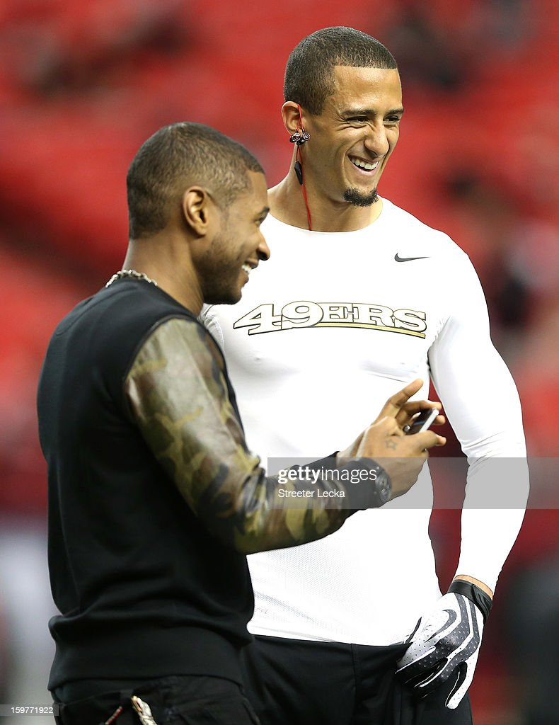 Singer Usher talks with quarterback Colin Kaepernick #7 of the San Francisco 49ers on the field prior to the 49ers playing against the Atlanta Falcons in the NFC Championship game at the Georgia Dome on January 20, 2013 in Atlanta, Georgia.