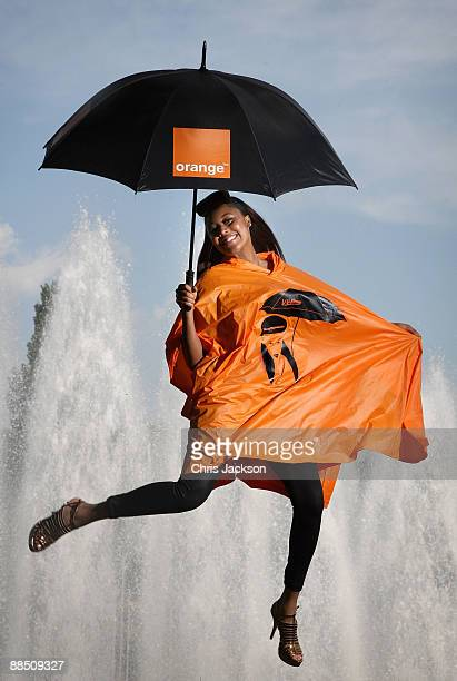 Singer VV Brown and Orange unveil a limited edition rain poncho designed by the style icon for Glastonbury festivalgoers during a photo call at...