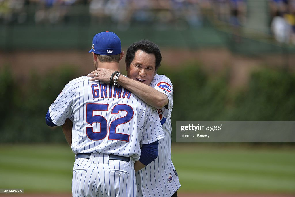 Singer Wayne Newton hugs Justin Grimm of the Chicago Cubs after throwing out a ceremonial first pitch before the game against the Pittsburgh Pirates...