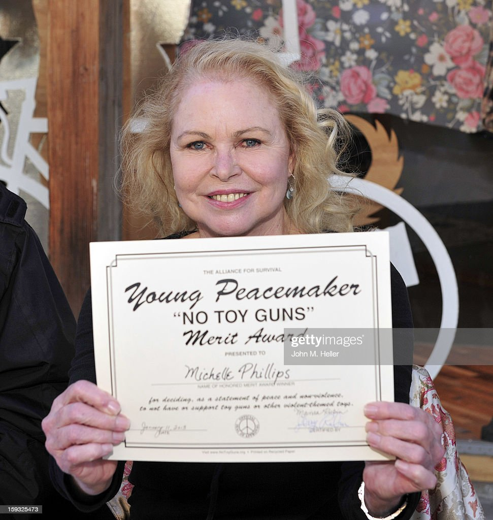 Singer/actress Michelle Phillipa a logntime anti-toy gun activist receives the 'No Toy Guns' Merit Award at the 'No Toy Guns' news conference on the Third Street Promenade on January 11, 2013 in Santa Monica, California.