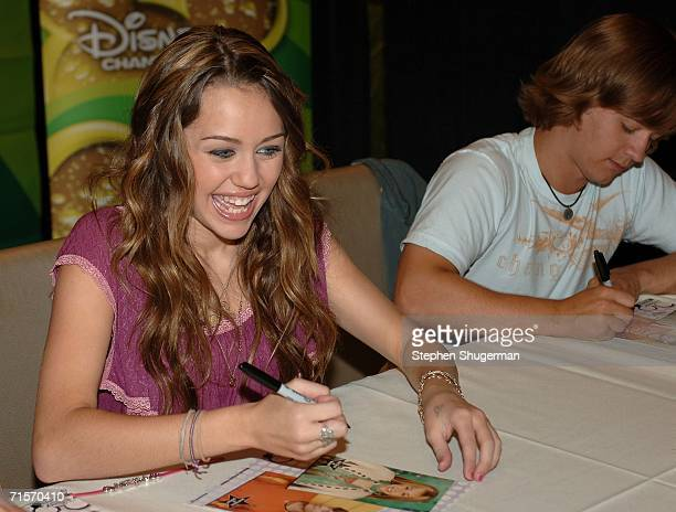 Singer/actress Miley Cyrus and actor Jason Earles of the show 'Hannah Montana' sign autographs inside at the Hollywood Radio Television Society 'Kids...