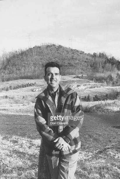 Singer/comedian Tennessee Ernie Ford wearing plaid buffalo jacket while standing in field in hometown